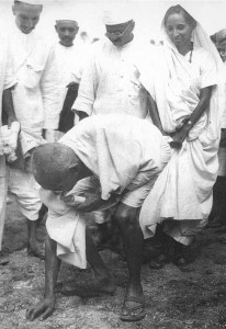 Gandhi picking up salt at the end of the march. Both men and women took part.